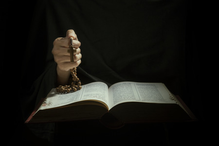 Hands holding rosary beads and cross while reading bible