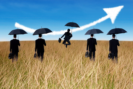 Successful insurance agent with umbrella and arrow up on the field photo