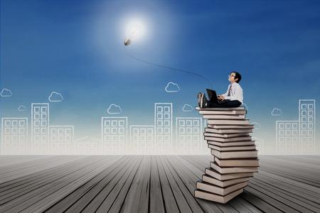 Kleines Kind auf dem Stapel der Bücher sitzt und mit einem Laptop
