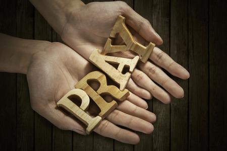 wort: Mann hält Wort beten in der Handfläche mit Holzuntergrund Lizenzfreie Bilder