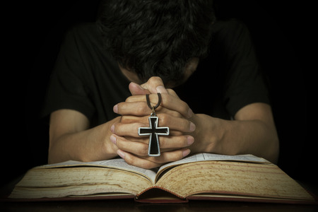 Closeup of man praying on bible while holding a cross photo