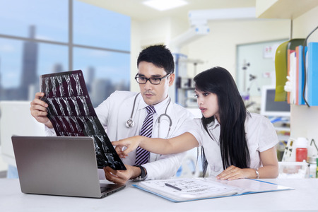 Healthcare, medical and radiology concept - two doctors looking at x-ray Stock Photo - 26324455