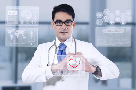 Portrait of medical doctor showing heart shape photo