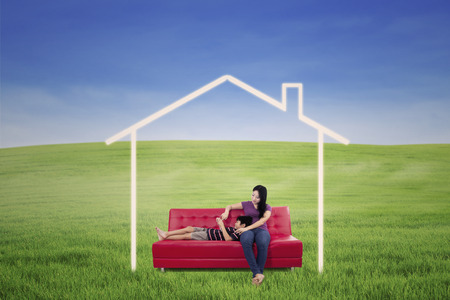 Mother and son relaxing on red sofa outdoor with house picture photo