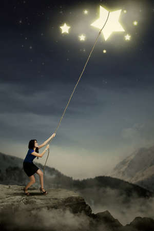 Portrait of young businesswoman taking stars from the sky space photo