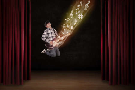Man playing electrical guitar jumping on a stage Stock Photo - 26544862