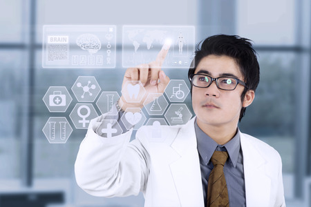 futuristic man: Doctor pushing a button on virtual display