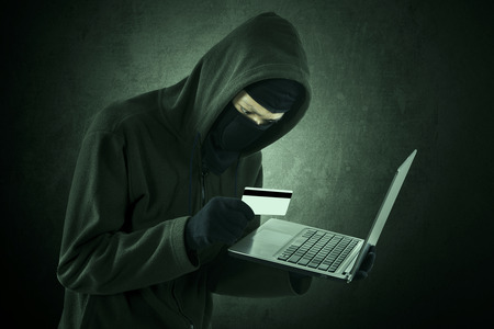 Man wearing a hoodie and holding credit card with a laptop photo