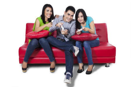 Three young teenagers playing video games together photo