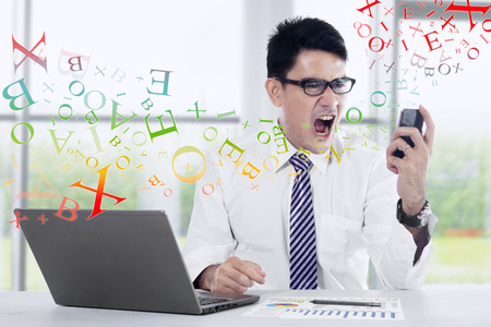 filipino adult: Angry young businessman looking at cell phone in office
