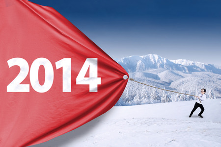Asian child is pulling big banner of new year 2014 on the snow mountain photo