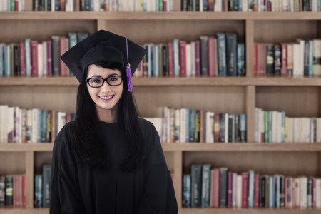 Beautiful Asian female graduate smiling at library photo