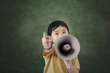 Boy and megaphone in front of blank board in class