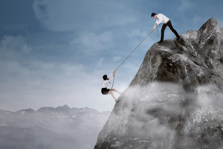 Portrait of businessman help his partner to climb the cliff by pulling her with a rope Stock Photo