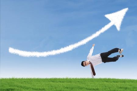 upturn: Businessman perform success move under up arrow cloud outdoor Stock Photo