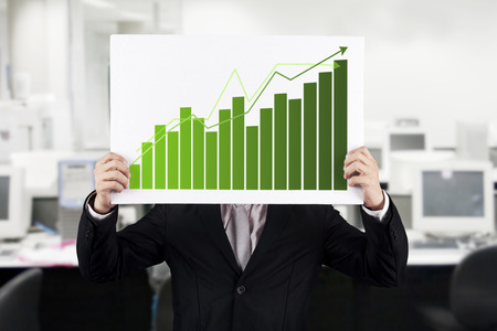 Young businessman with growth chart at office photo