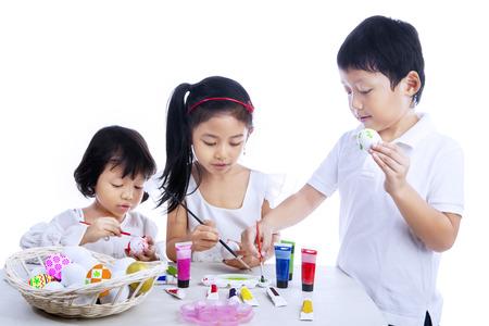 niños pintando: Niños que pintan los huevos de Pascua, aisladas sobre fondo blanco