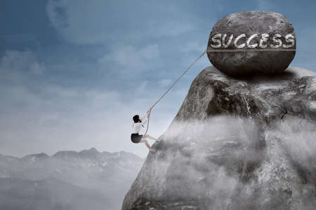 Businesswoman climbing steep mountain hanging on rope  Stock Photo