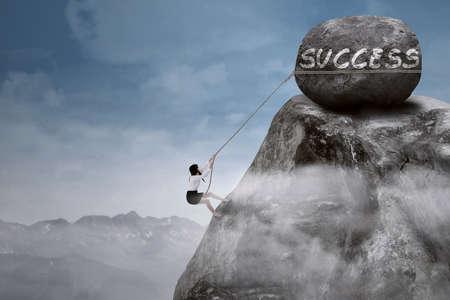 steep: Businesswoman climbing steep mountain hanging on rope  Stock Photo