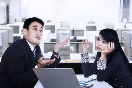 A man and woman working together with confused expressions on their faces photo