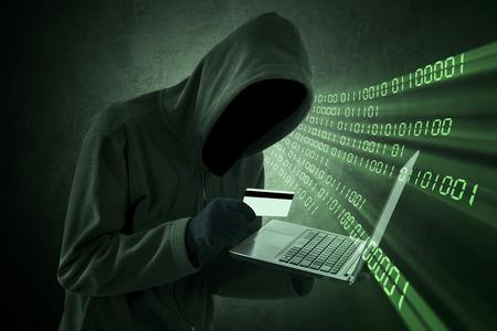 tarjeta de credito: Concepto de robo de Internet - Hombre que sostiene la tarjeta de cr�dito con el port�til en la mano
