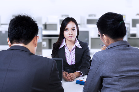 Two business people having a interview with job applicant photo