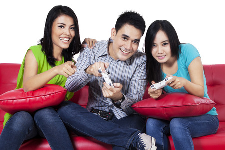 Three asian teenagers playing video games photo