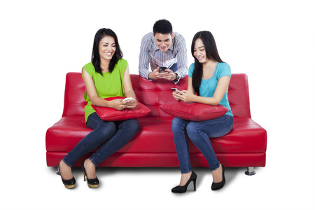 Three asian teenagers using mobile phone and sitting on red sofa photo