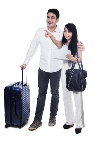 Young couple with suitcase looking at copy space on white background photo