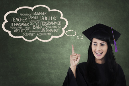 Happy student in graduation cap with her future career Stock Photo