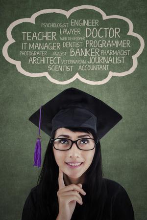 toga: Estudiante feliz en la tapa de graduación pensando en sus opciones de futuro profesional