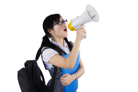 Portrait of a female student shouting via megaphone isolated on white background Stock Photo - 26657639