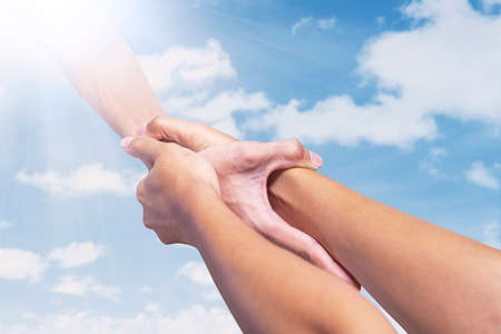 hands solution: Helping hand, male hand takes young female hand on blue sky