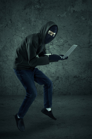 Criminal in dark clothes and balaclava is stealing a laptop computer Stock Photo