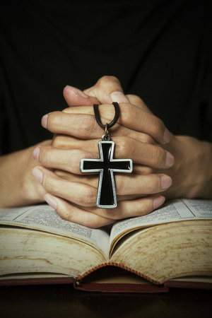 Closeup of hand praying pose on bible while holding a cross photo