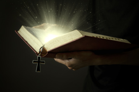 messiah: Hands of man holding holy bible and wooden rosary with magical rays Stock Photo