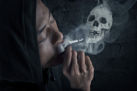 Young man smoking cigarette on dark background photo