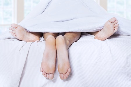 Close-up of couple's feet having intimate relation in bed photo