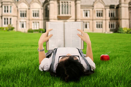 indian student: A female college student reading a book while lying on the park