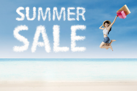 Girl jumping beside summer sale cloud on white sand photo