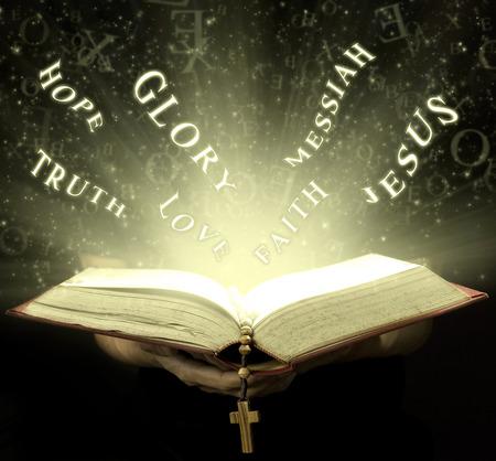 Handen van de man die de heilige Bijbel en houten rozenkrans met magische stralen Stockfoto