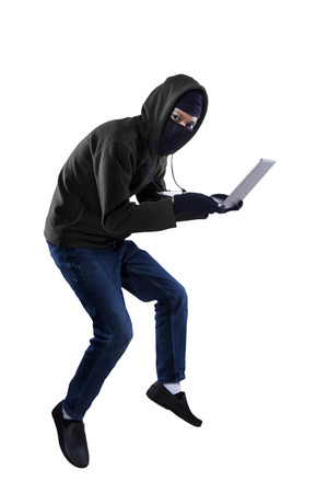 swindled: Criminal in dark clothes and balaclava is stealing a laptop computer Stock Photo