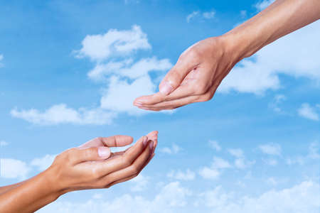 Assistance concept with helping hand on blue sky photo