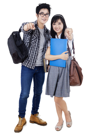Happy trendy college students with bags and books, posing together, pointing at camera, photo