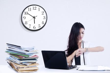 administración del tiempo: Negocios con exceso de trabajo que mira un reloj. disparar a los lugares de trabajo