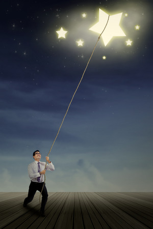 Young businessman taking a star from the sky space as a concept of high achievement photo
