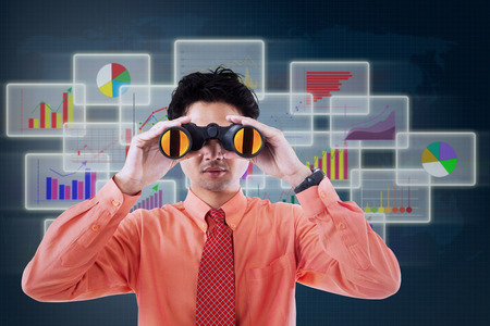 Businessman see vision using binoculars in front of business futuristic background photo