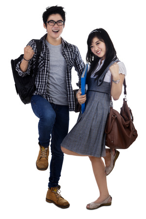 Happy trendy college students with bags and books, expressing success photo
