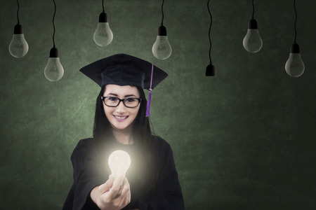 bright future: Happy female graduate giving bright light bulb in class as hope of bright future