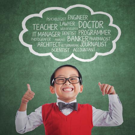 bambini pensierosi: Studente di scuola elementare con espressione orgoglioso mostrando i suoi ideali sopra la sua testa Archivio Fotografico